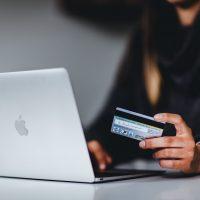 credit score woman holding black smartphone near silver macbook