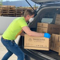 Delivery Management man in green t-shirt and blue denim jeans holding brown cardboard box