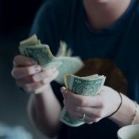 Personal Finance focus photography of person counting dollar banknotes